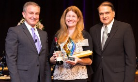 Shannon Kucharski from San Clemente Cove receives her award on stage with David Brown and Nigel Lobo