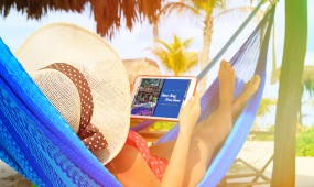 A woman in a hammock in a tropical destination is looking at an iPad showing Time Together, the Grand Pacific Resorts owner magazine.